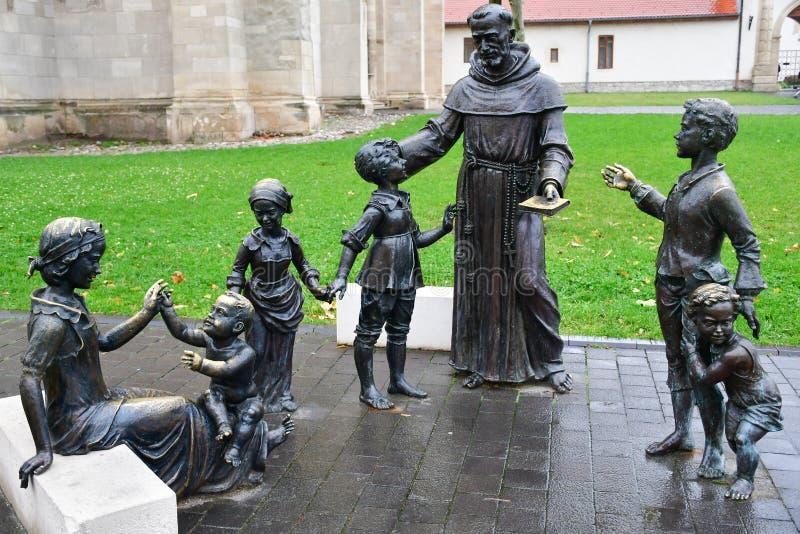 Bronzestatue der Frau, des Priesters und der Kinder stockbild