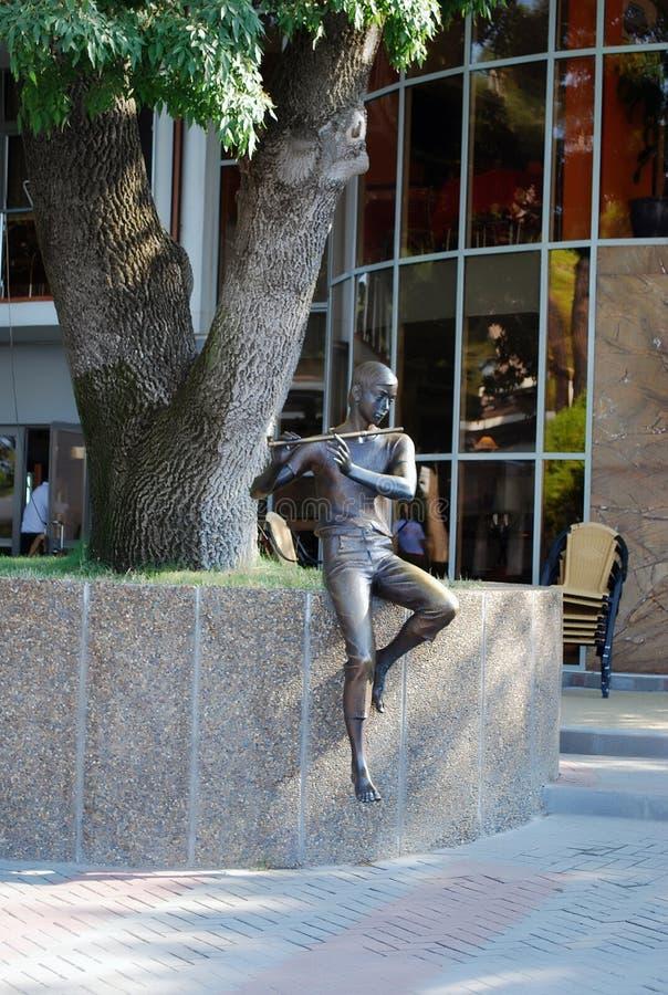 Bronzestatue eines Jungen, der Flöte im Erholungsgebiet am Gelendzhik-Stadtdamm spielt lizenzfreie stockfotografie