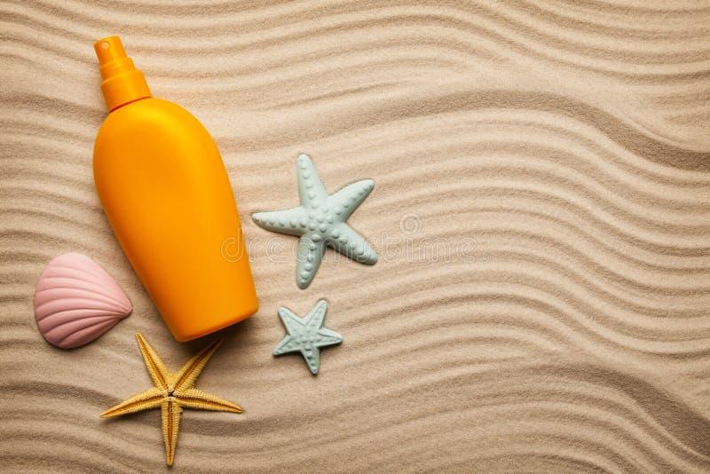 Bronzez l'huile dans une bouteille jaune et des coquillages photo stock