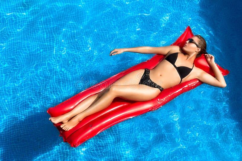 Bronziert. Schönheit Brunette, der im Pool ein Sonnenbad nimmt lizenzfreie stockfotos