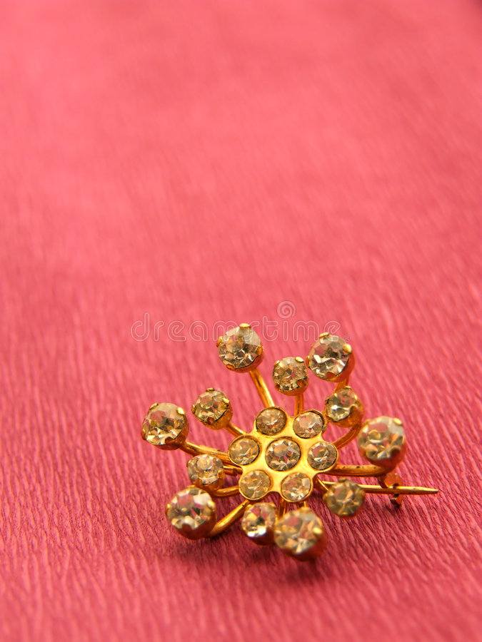 Brooch. Golden brooch over pink background royalty free stock image