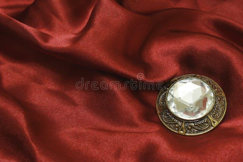 Brooch con lo zircon su seta rossa fotografia stock libera da diritti