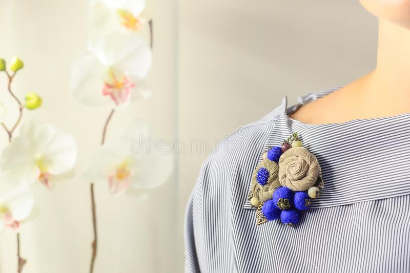 Brooch handmade in the form of flowers beige and blue color is attached to the female blouse royalty free stock photo