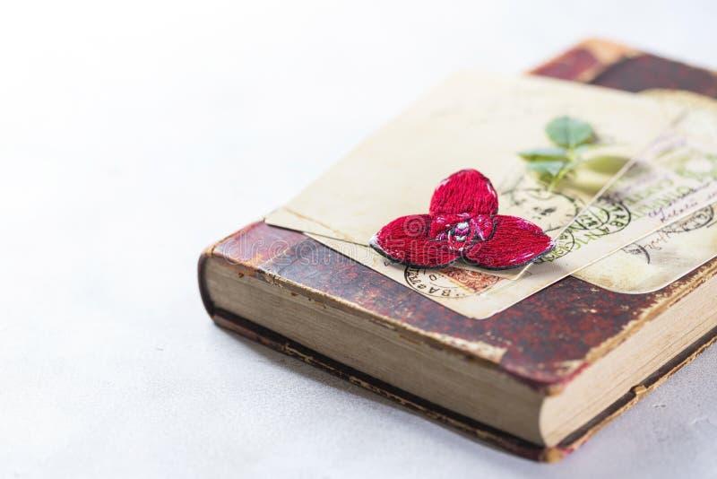 Brooch orchid, rode lycast, op een wijnboek Handgemaakt stock fotografie