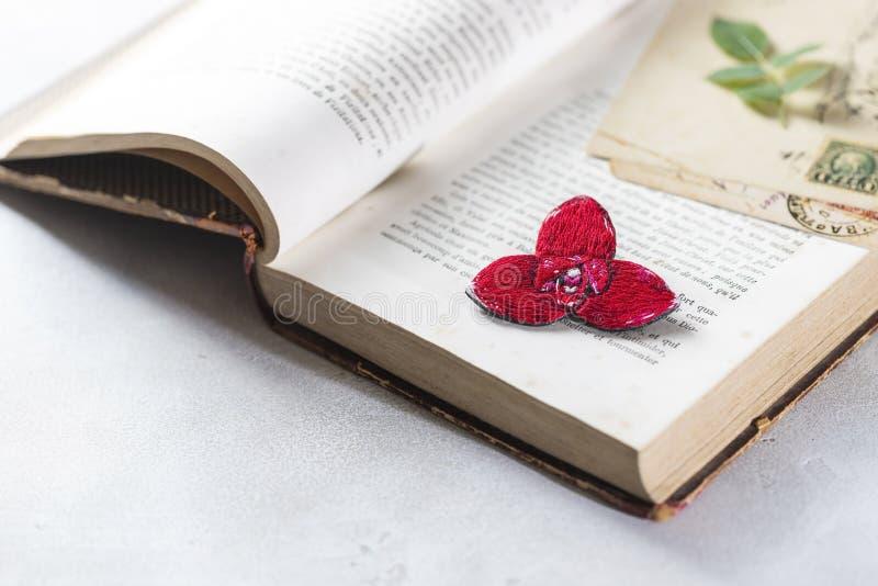 Brooch orchid, rode lycast, op een wijnboek Handgemaakt stock afbeelding