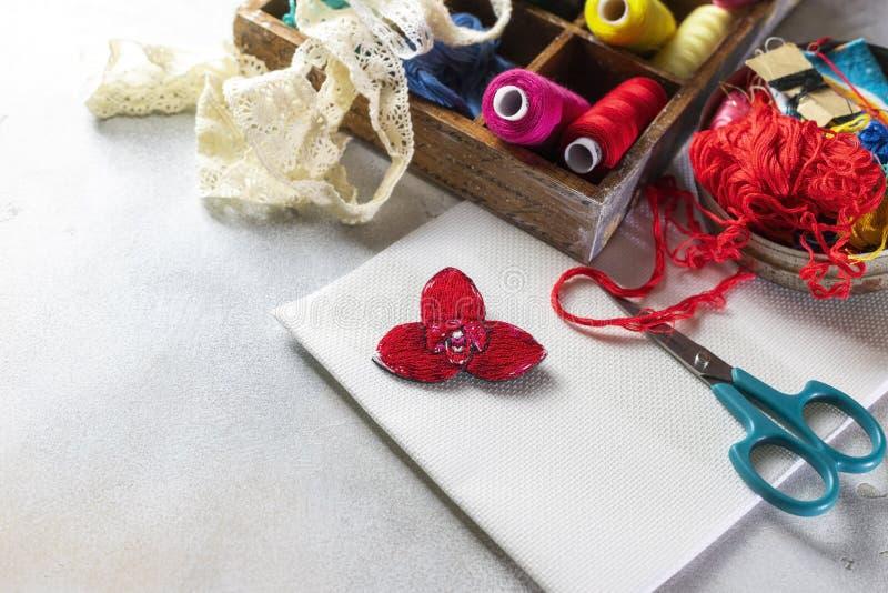 Brooch orchid, rode lycasta, op de achtergrond van materialen voor naaldwerk royalty-vrije stock afbeelding