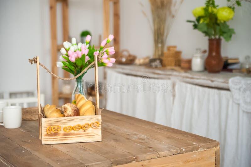Brood in een geweven houten doos in de keuken in een rustieke stijl Ontbijt, brood, witte koppen binnen heldere Scandinavi stock foto