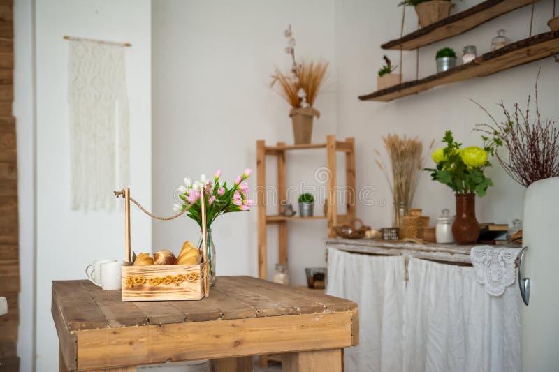 Brood in een geweven houten doos in de keuken in een rustieke stijl Ontbijt, brood, witte koppen binnen heldere Scandinavi royalty-vrije stock afbeeldingen