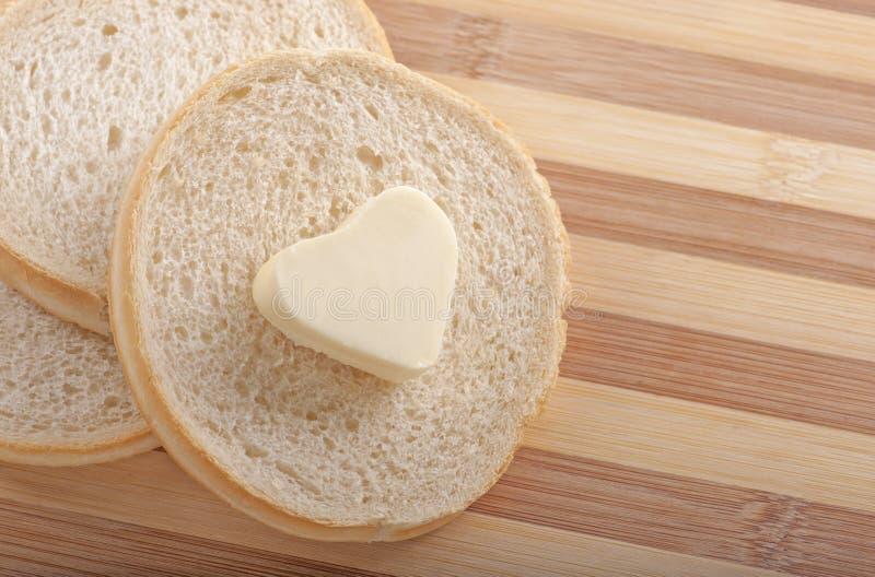 Brood en hart gevormde boter stock foto