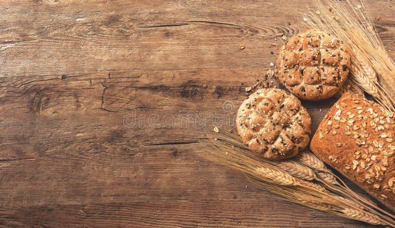 Brood en koekjes met tarwe op een houten oppervlakte met ruimte voor tekst royalty-vrije stock afbeeldingen