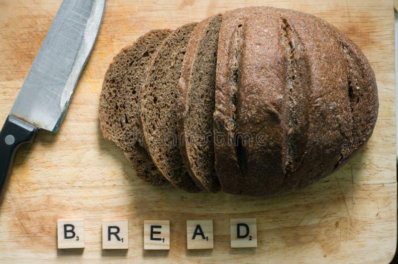 Brood en mes op houten lijst stock foto's