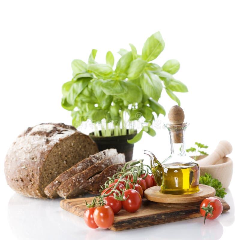 Brood, kruiden, olijfolie en groenten stock fotografie