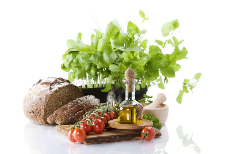 Brood, kruiden, olijfolie en groenten royalty-vrije stock foto