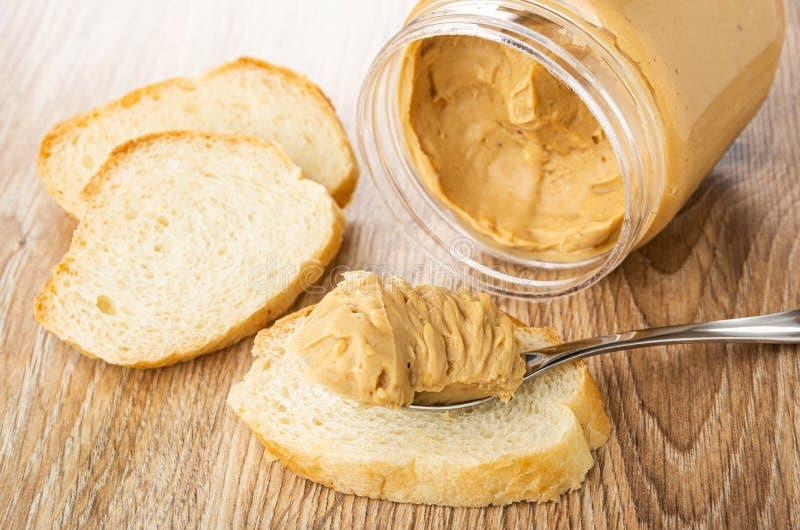 Brood, lepel met pindakaas op boterham, plastic kruik met pindakaas op houten lijst royalty-vrije stock foto