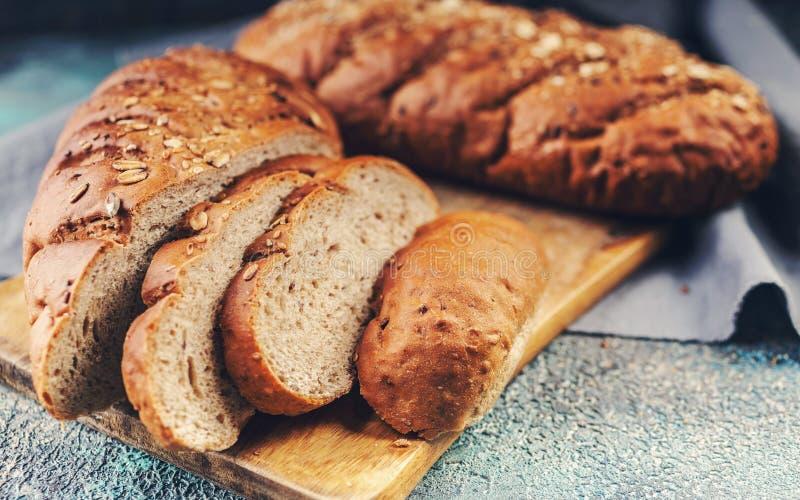 Brood met graangewassen op een houten scherpe raad royalty-vrije stock afbeelding