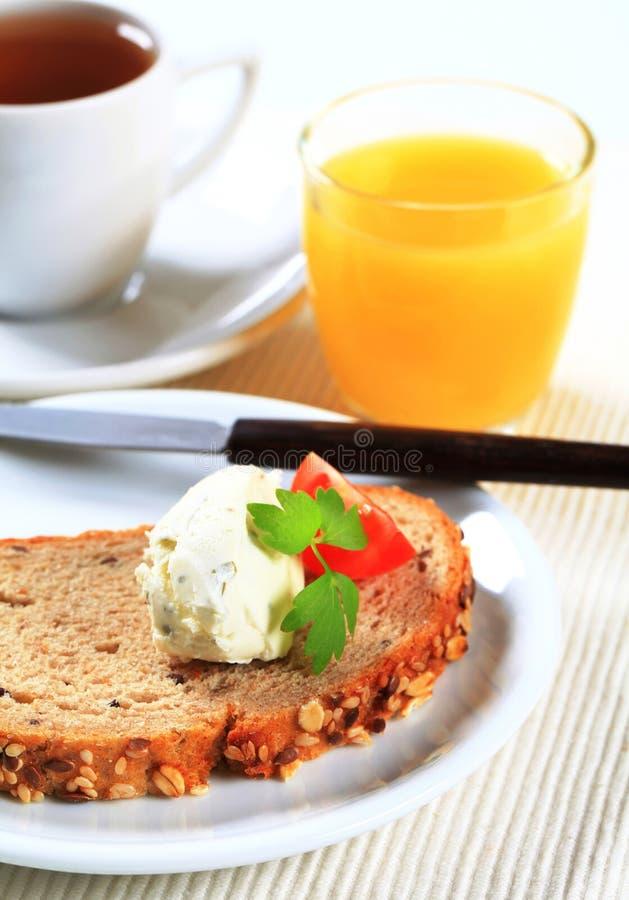 Brood met uitgespreide kaas, kop thee en jus d'orange stock foto's