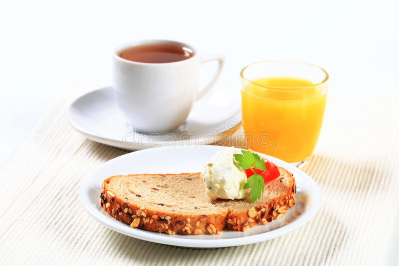 Brood met uitgespreide kaas, thee en jus d'orange royalty-vrije stock afbeelding