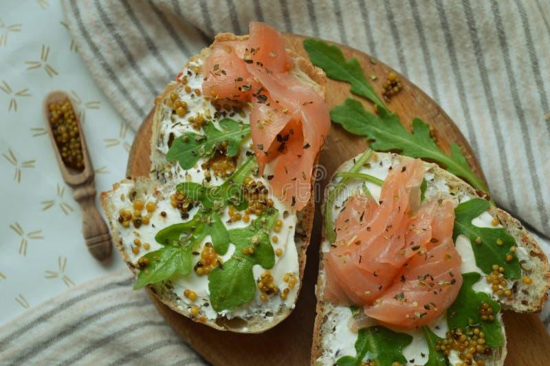 Brood met zalm, mosterdzaden, arugula en roomkaas stock afbeelding