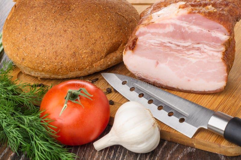 Brood, stuk van borststuk, tomaat, kruiden, dille, knoflook, mes op scherpe raad op houten lijst stock fotografie