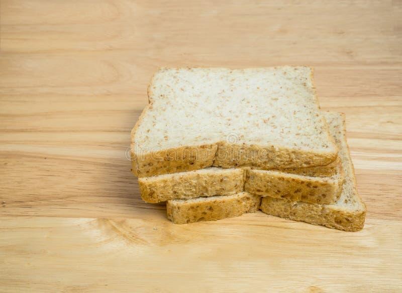 Brood van de drie plak het gehele tarwe op houten lijst royalty-vrije stock afbeeldingen