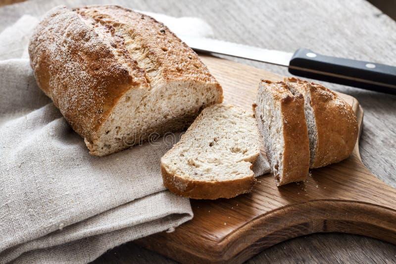Brood van geheel tarwebrood met plakken op houten raad stock foto's