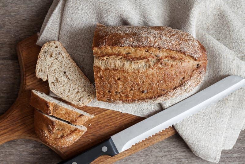Brood van geheel tarwebrood met plakken op houten raad op keukenlijst royalty-vrije stock foto