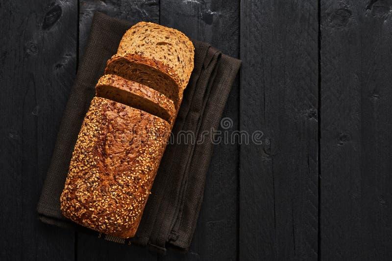 Brood van gesneden geheel tarwebrood op donkere dishtowel over zwarte wo royalty-vrije stock foto