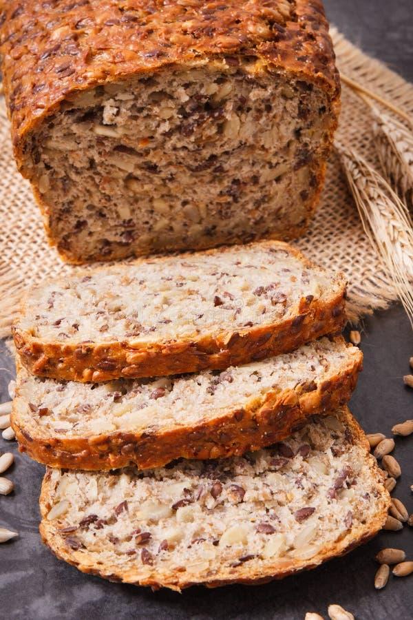Brood van wholegrain brood voor ontbijt, ingrediënten voor baksel en oren van rogge of tarwekorrel royalty-vrije stock foto