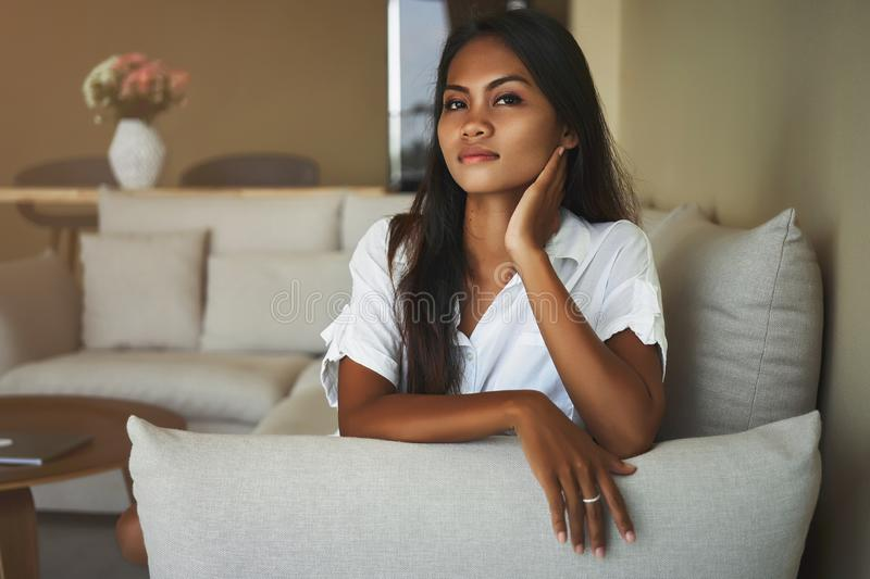 Brooding young Asian woman is siting on couch at home in the living room royalty free stock images