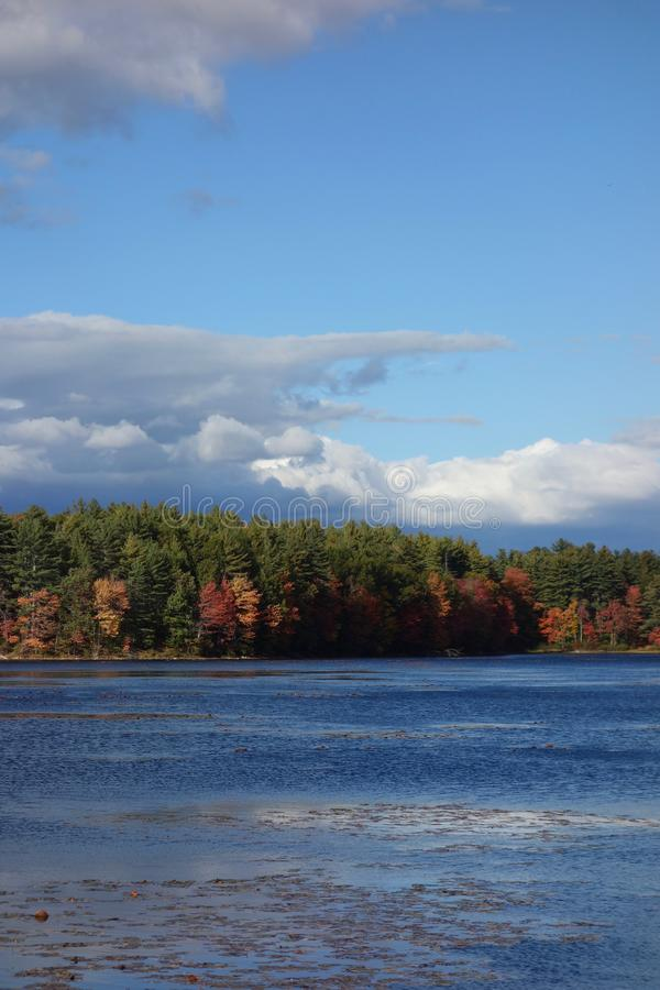 Brooding clouds hanging over a dark blue lake in autumn stock photography