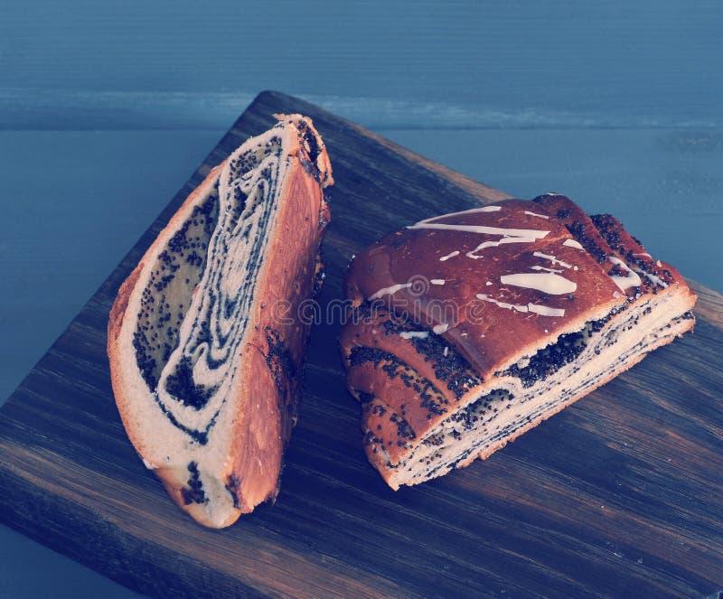 Broodje met papaverzaden, besnoeiing in de helft op houten stock foto's