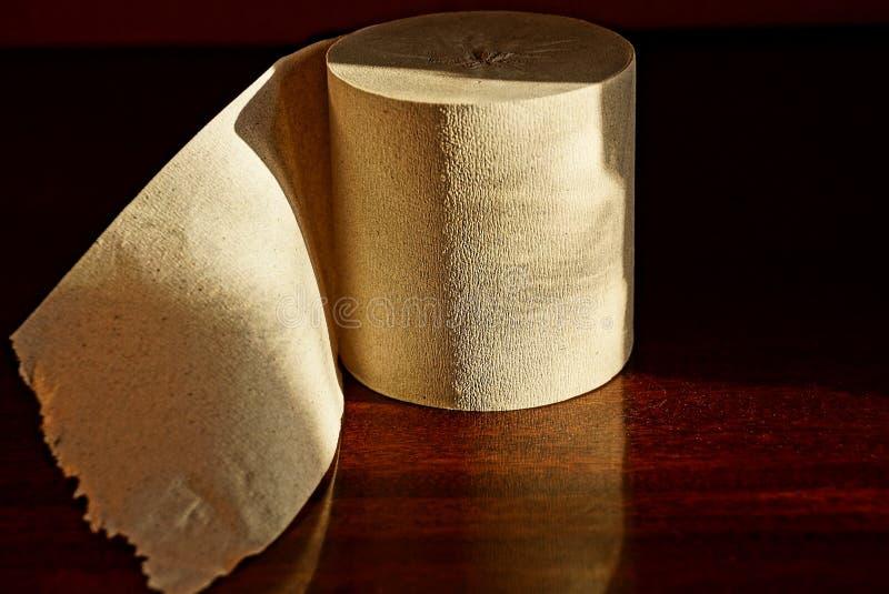 Broodje van grijs toiletpapier op een bruine lijst stock fotografie