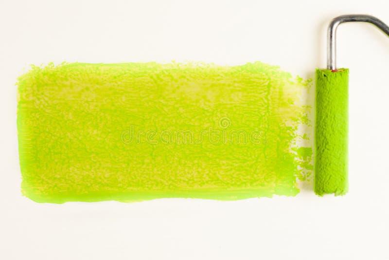 Broodje voor verf en groen spoor op muur Het concept van de reparatie stock afbeeldingen