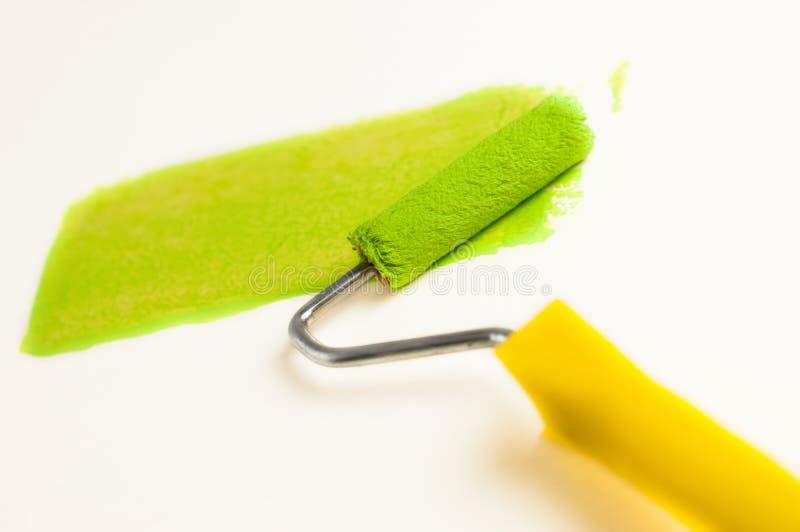 Broodje voor verf en groen spoor op muur Het concept van de reparatie stock foto's