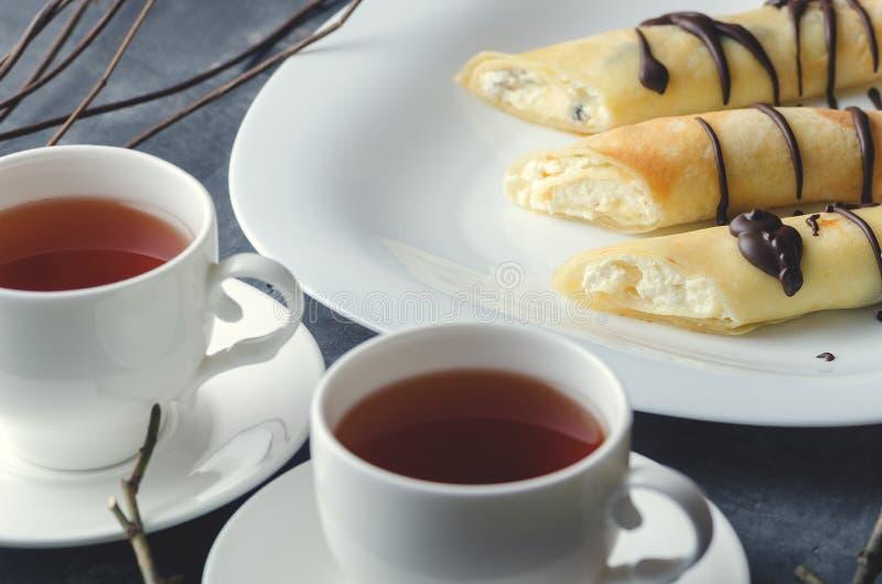 Broodjes met kwark en chocolade naast twee kop theeën Close-up cropping royalty-vrije stock afbeelding