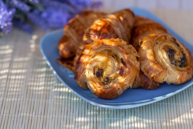 Broodjes met rozijnen en Franse croissants op een blauwe plaat Dessert royalty-vrije stock foto's