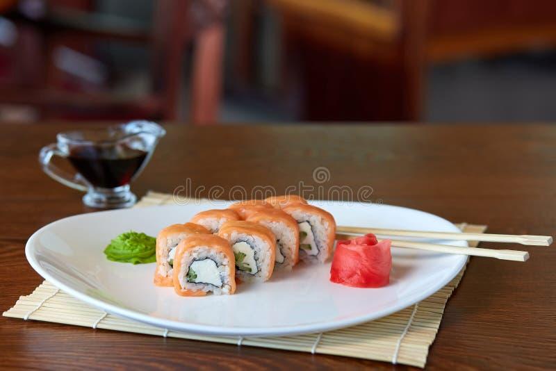 Broodjes met zalm, rijst, norialgen, roomkaas en komkommer, die op een witte plaat met wasabi en ingelegde gember liggen stock afbeeldingen