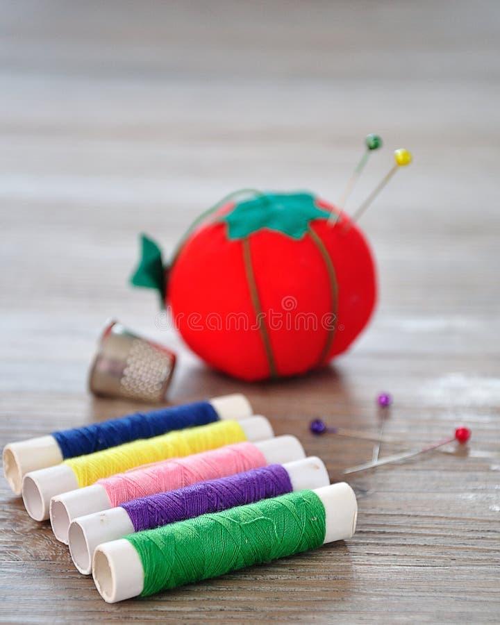 Broodjes van draad met uit het kussen van de nadrukspeld als rode tomaat en vingerhoedje wordt gevormd dat royalty-vrije stock afbeelding