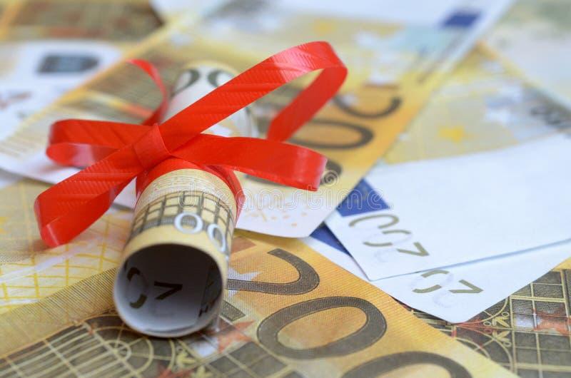 Broodjes van geld in een giftlint op rekeningen van dollars en euro royalty-vrije stock afbeelding
