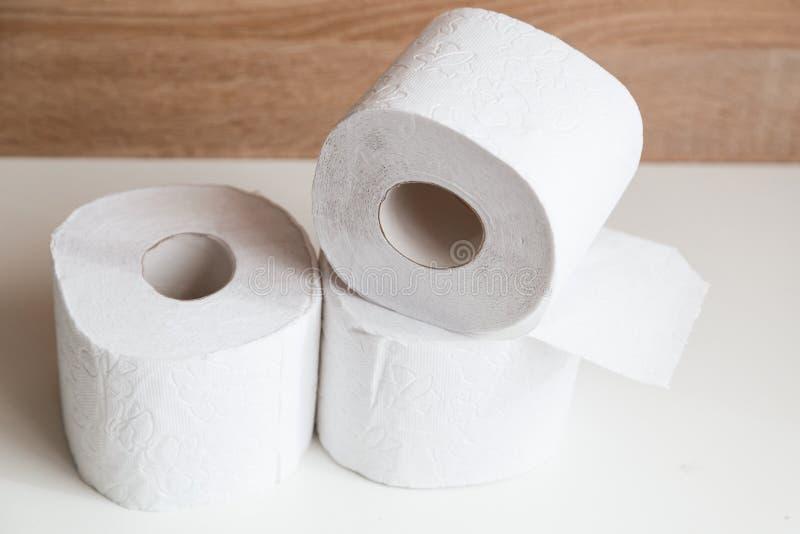 Broodjes van wit toiletpapier op witte en houten achtergrond stock foto