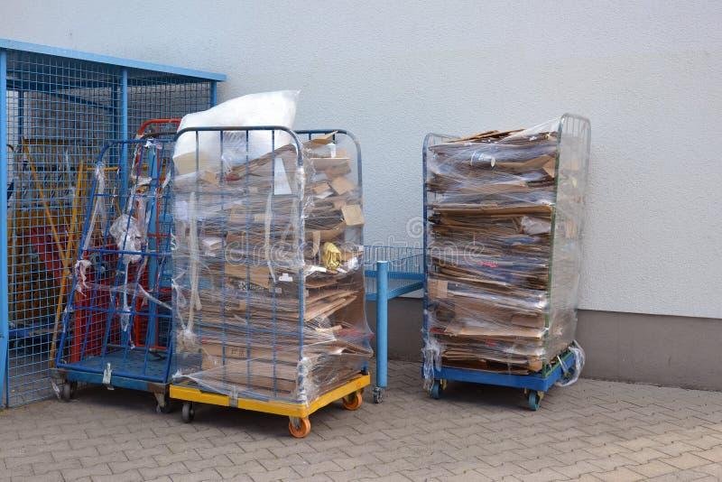 Broodjescontainers met gestapeld papierafval en oude kartondoos naast een opslag royalty-vrije stock foto