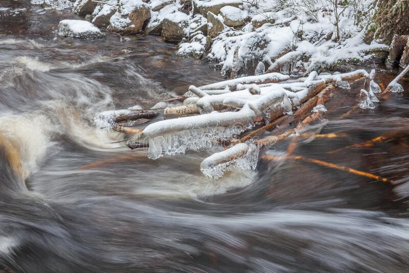 Brook of water in winter nature. Cold stream water flows between snowed stones. long shutter speed. The flowing of water in waterfall with snow and some water royalty free stock photos