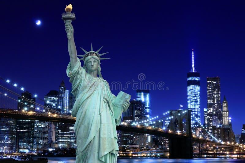 Brooklyn överbryggar och statyn av frihet på natten royaltyfria foton