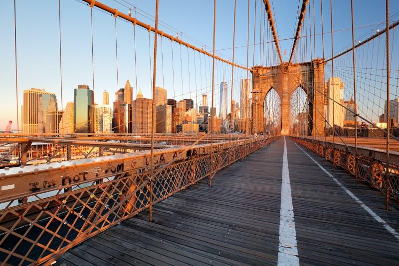 Brooklyn-Brücke über East River sah von der New- York Citylower manhattan-Ufergegend bei Sonnenuntergang an stockfotos