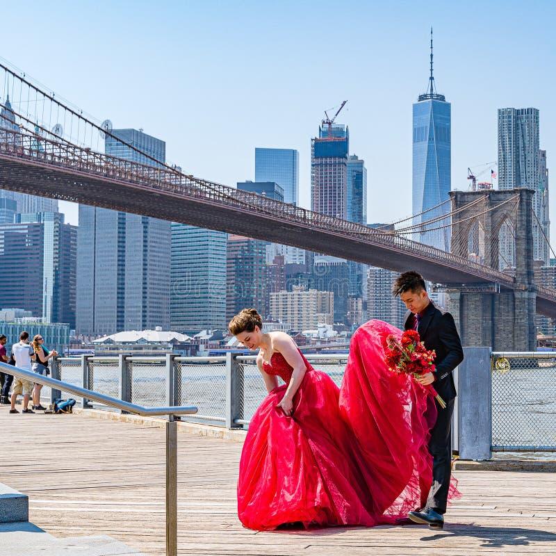 Brooklyn-Brücke mit unteren Manhattan-Skylinen, Modesitzung mit einem enormen roten Kleid in New York City stockfotografie