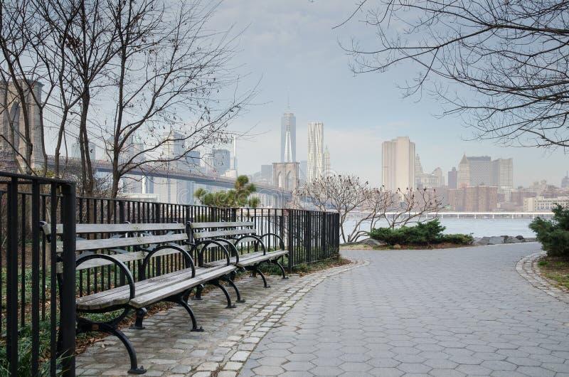 Brooklyn-Brücken-Park-Bank und Gehweg mit Manhat lizenzfreie stockfotografie
