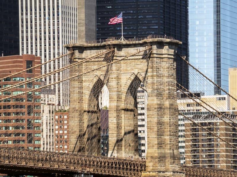 Brooklyn-Brücken-Turm mit USA-Flaggen-, Manhattan-Gebäudehintergrund früh morgens mit blauem Himmel und Sonnenglanz stockbilder