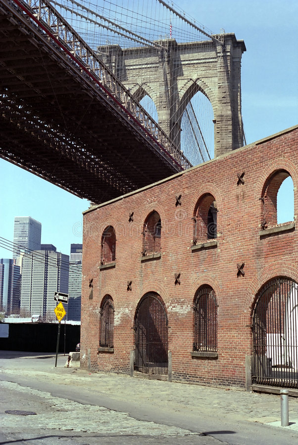 Brooklyn Bridge Dumbo New York USA. Brooklyn Bridge towers above the old tobacco warehouse on the East River, Dumbo district of Brooklyn, New York. Manhattan in stock image
