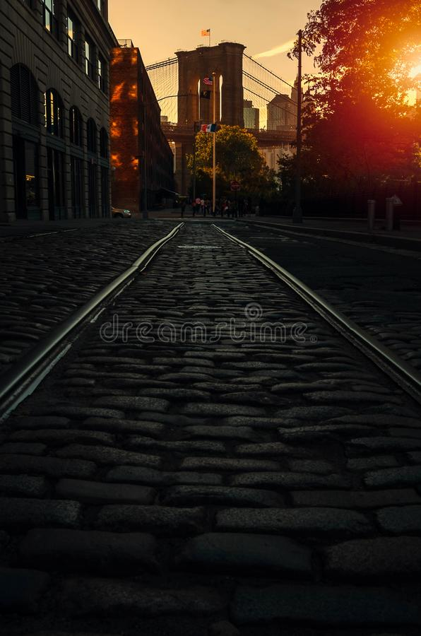 Brooklyn bridge on a sunny day. Empty cobblestone street with Brooklyn bridge on a sunny day royalty free stock images