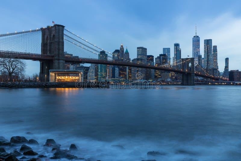 Brooklyn bro i det Manhattan centret med Cityscape på en dimmig molnig dag på solnedgången New York USA royaltyfri fotografi
